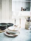 Geschirr und Besteck auf Tisch in Landhausküche