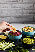 Dipping pita bread in beetroot hummus
