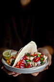 Hands holding Mexican Tacos with fresh vegetables and chicken on dark background