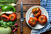 Fresh organic vegetables on a dark wooden table with tomatoes in a bowl and a knife