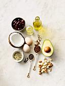 Auswahl gesunder Fette: Ei, Samen, Kokosnuss, Speiseöl, Nüsse und Bohnen