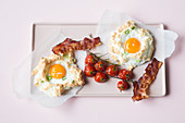 Eggs on 'clouds' with oven-roasted tomatoes and bacon (keto cuisine)