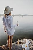 Frau im Strandkleid mit Sektglas am Felsufer eines Sees