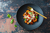 Gnocchi with pumpkin, spelled, tomatoes, garlic and parmesan