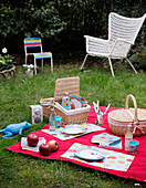 Place mats and floral picnic plates and cups on red blanket in garden