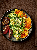 Saddle of venison with a mango and rocket salad and nachos