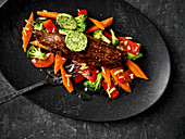 Venison fillet with colourful honey-glazed vegetables and herb butter
