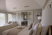 Beigefarbenes Schlafzimmer in Strandhaus mit Badezimmer abgetrennt durch Lamellentüren