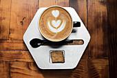 Cappuccino mit Milchschaumherz auf sechseckigem Teller
