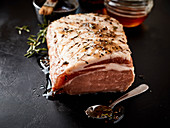 Raw pork collar roast marinated with honey, allspice and fennel