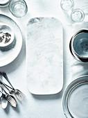Weißes Geschirr, Gläser, Besteck und Marmor-Servierplatte auf Tisch