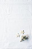 Anhänger und Sterne auf weißer Tischdecke