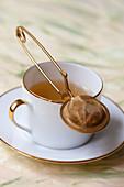 Goldrand-Tasse mit Tee und Teesieb