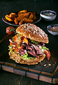A burger with roast beef, lobster and potato wedges
