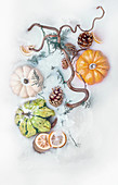 Colorful pumpkins and orange slices with cones and tree branches in milk bath