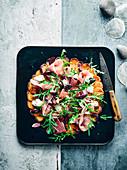 Süsskartoffel-Pizza mit Oliven und Serranoschinken