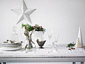 Weihnachtsdekoration, Geschirr, Gläser und Besteck auf weissem Holztisch