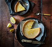 Lemon Tart with slice taken out Slice on plate with lemons