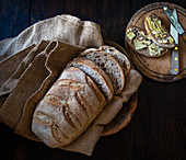 Sourdough Organic Bread in a bread basket with slices of buttered bread