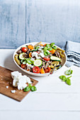 Pasta salad with peas, zucchini, minced meat and feta