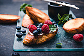Toasted baguette slices with almond cream cheese, berries and mint (vegan)