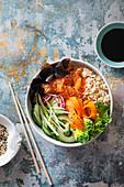 Sushi buddha bowl with salmon, brown sushi rice, nori nori, cucumber, radish, carrot and spring onion