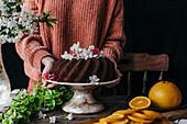 Schokoladen-Kranzkuchen dekoriert mit Obstblüten auf Kuchenständer