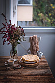 Stack of crepes and a cup of coffee on rustic wooden table