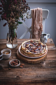 Stack of crepes with melted dark chocolate and pecans and a cup of coffee on a rustic wooden table