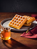 A plate with 3 belgian waffles being sprinkled with powdered sugar Pitcher of maple syrup in foreground Warm, moody lighting on wood tabletop