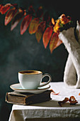 Cup of black coffee espresso standing on white table cloth in dark room with autumn leaves and flowers in clay vase, old books