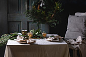 Christmas or New year table setting with empty ceramic plates, napkins, Christmas thuja wreath, luminous garland and burning candles