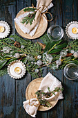 Christmas or New year table setting with empty ceramic plates, glasses, napkins, Christmas thuja wreath, luminous garland and burning candles on dark wooden plank table. Holiday mood. Flat lay