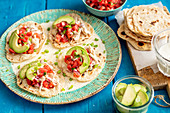 Home made tortillas with shredded cooked chicken, avo and tomato salsa