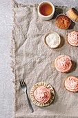 Homemade cupcake with pink buttercream and coconut flakes on ceramic plate