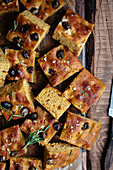 Italian pumpkin focaccia with olives and rosemary on a wooden board