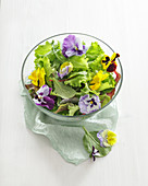 Mixed salad and edible flowers in a glass bowl