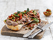 Sandwich rolls with roast beef and bell pepper-zucchini salsa on a wooden board