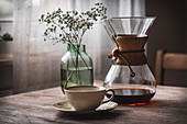A chemex carafe, a coffee cup and a glass vase on a wooden table
