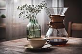 Chemex-Karaffe mit Kaffee, Kaffeetasse und Glasvase auf Holztisch