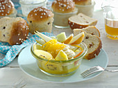 Fruit salad in a small bowl, with homemade raisin rolls