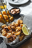 Fried small octopuses served in fryer basket with lemon