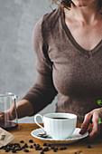 Frau mit Kaffeetasse, Glaskanne und Kaffeebohnen