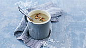 Wintry mushroom cream soup in a metal cup with a spoon