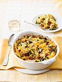 Fusilli casserole with salami, romaine lettuce and arugula