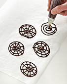 Piping chocolate decorations onto baking paper