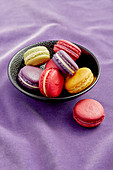 Macarons in a black bowl on a purple background