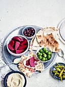 Eingelegte Rote Bete, Oliven und Peperoni mit Fladenbrot und Hummus