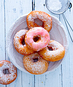 Donuts with pink icing and powdered sugar