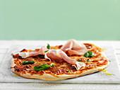 Pizza mit Parmaschinken und Basilikum